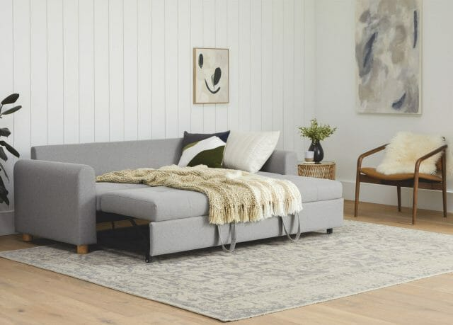 The Article Nordby sofa bed is shown set up with blankets and pillows