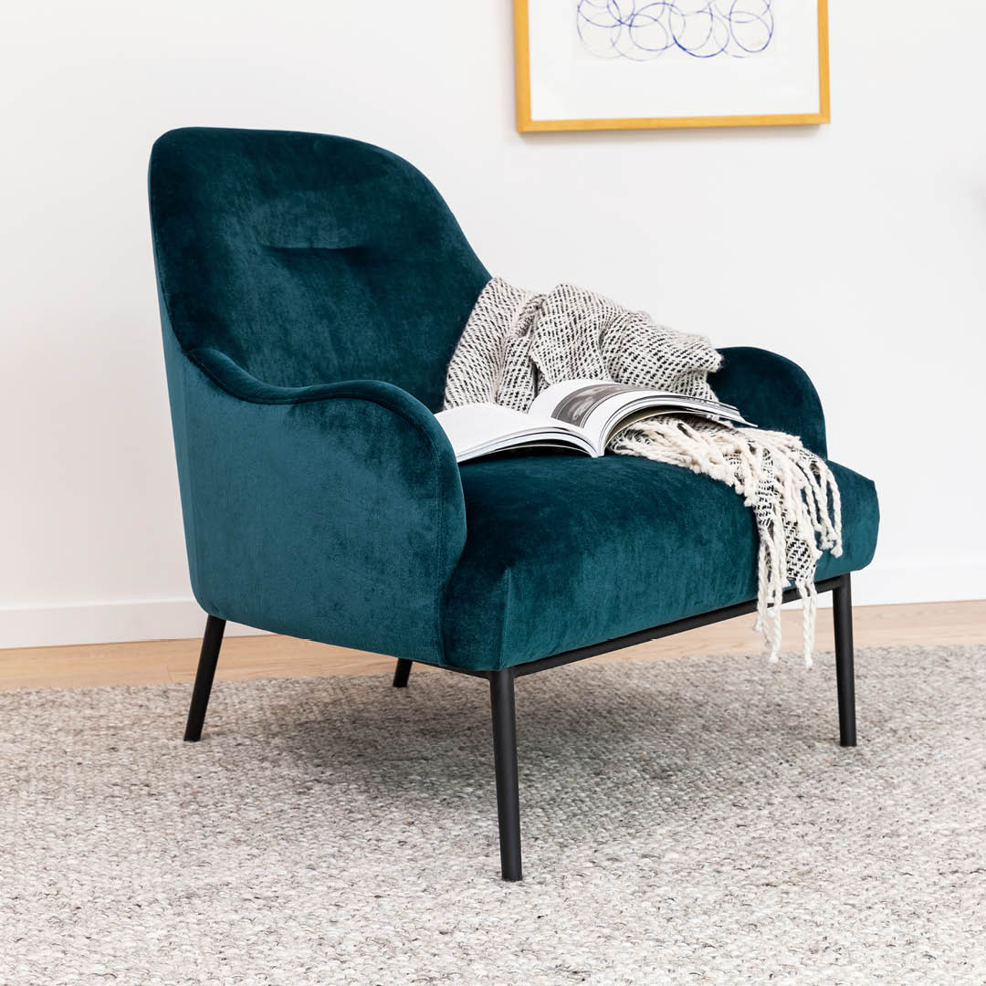 The Mercury Blue Embrace chair, styled against a white wall with a gray rug and a framed photo in the background.