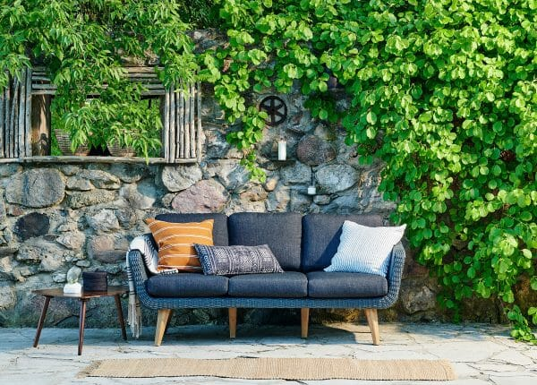 Lynne Knowlton's Ora sofa looks gorgeous against the background of stone and ivy. The Amoeba table next to the sofa ties it all together.