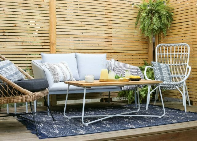 Emily's backyard patio brings airy design and boho vibes together. The rattan Aeri lounger nicely compliments the light Palo loveseat, while the palette of whites, grays, and dark accents keep the space grounded. Tie the room together with that lovely Nimbus table.