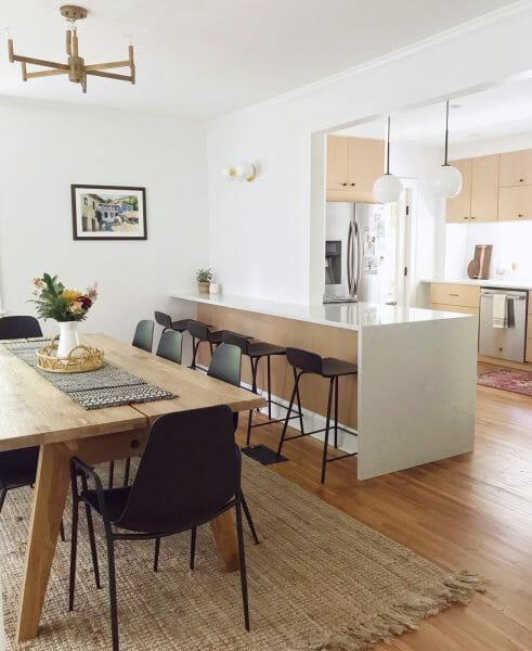 Anga Jayne creates separation of dining room and kitchen with subtle cues. The rug demarcates the dining area, while the black stools and Svelti chairs indicate two separate areas. Ps: nice Madera dining table.
