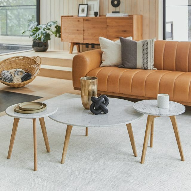 A tan leather sofa sits center-right. Marble coffee tables sit in the foreground; a roughly finished sideboard sits in the background.