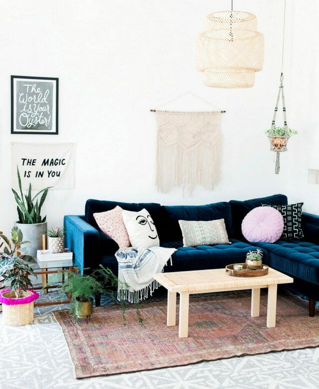 A blue velvet sofa looks beautiful in blogger Oh So Beautiful Paper's living room.