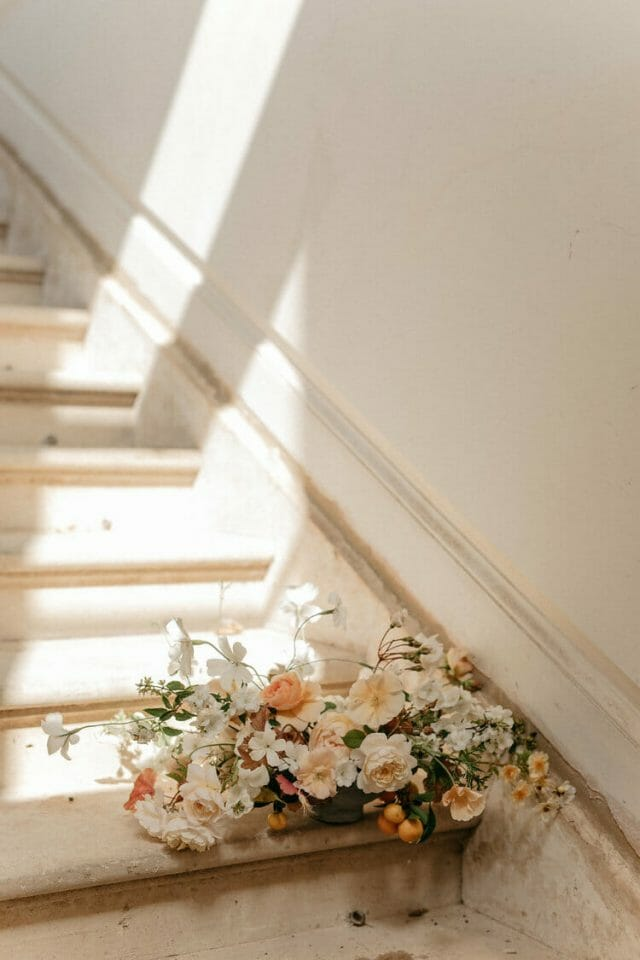 A bouquet of flowers sits on minimalist wooden stairs as the natural light shines in.