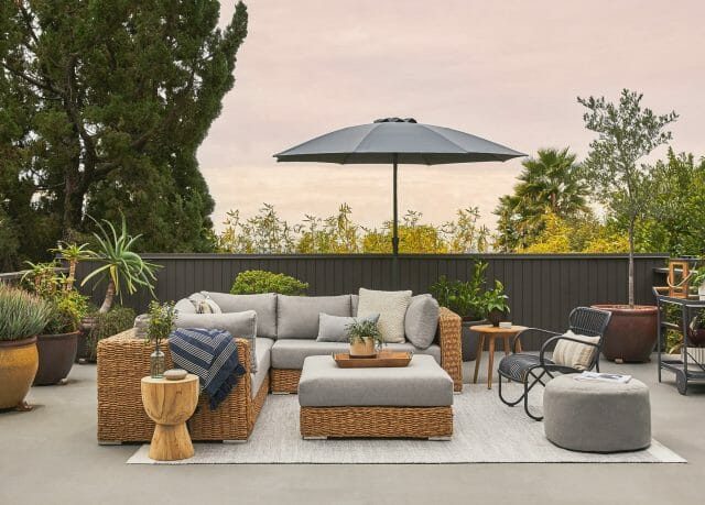 A large balcony is shown with a wicker sectional sofa, patio umbrella, and wicker lounge chair.