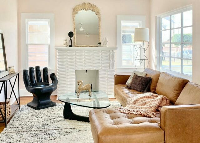 A living room features a Sven Charme Tan Sofa and a black hand chair.