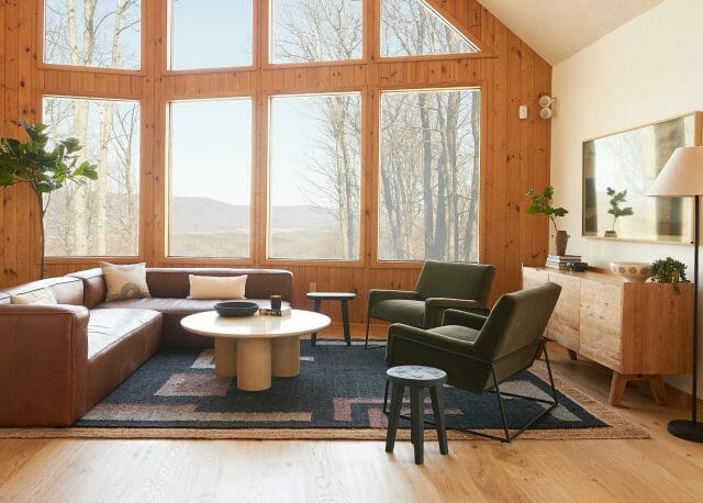 A cabin with timber walls and floor to ceiling windows features the Article Cigar Sectional.