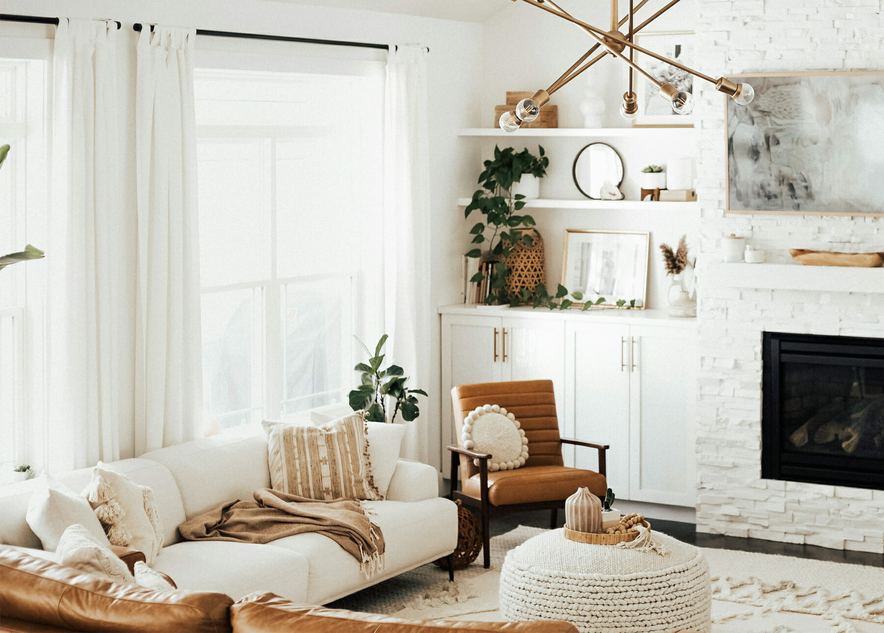 Amy E. Peters' boho living room features Article furniture, white built-in bookshelves and a fireplace