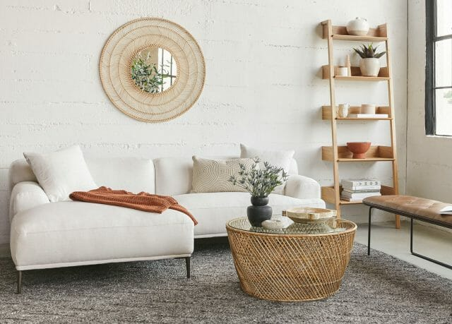 A white sectional sofa and rattan coffee table are featured in a white room.