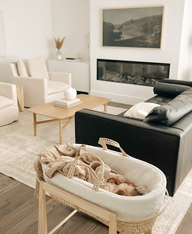 A living room features a baby sleeping in a bassinet, along with two white armchairs and a black sofa.