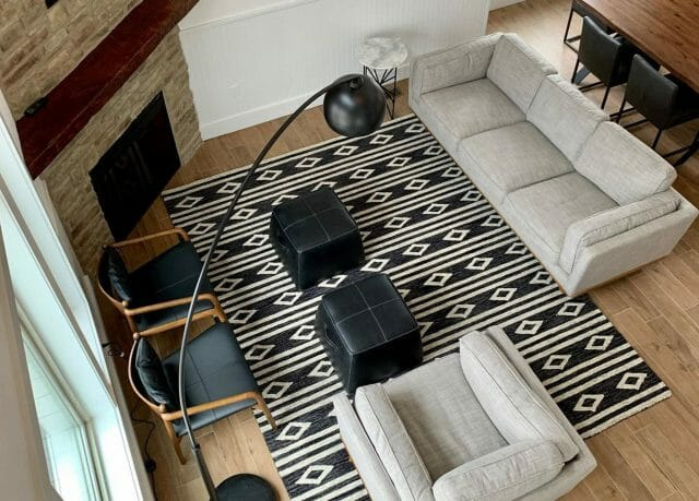 A graphic black and white rug is shown in a living space with a white Article sofa and black armchairs.