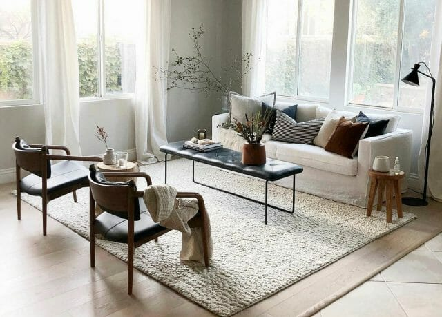 A black and white living room is shown, with two black armchairs, a white sofa, and a leather tufted bench as a coffee table.