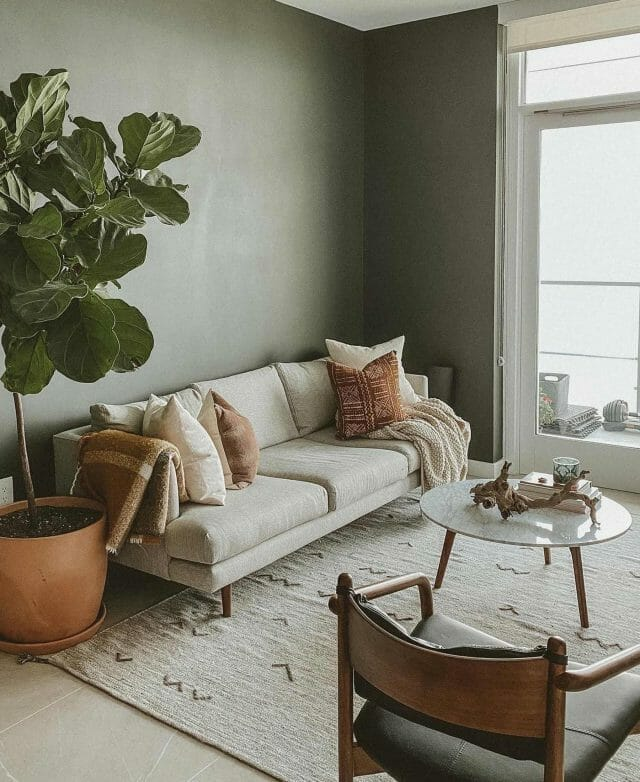 Blogger Travis Collins' minimalist living room features a light sofa, fiddle leaf fig, leather chair, and marble coffee table.