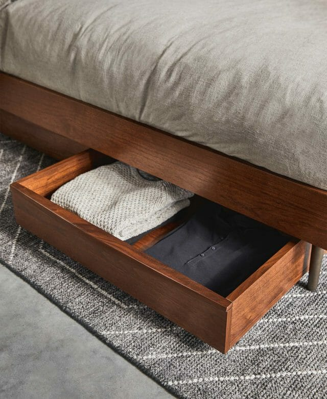 Article's Lenia Under Bed Storage Box in walnut is shown filled with sweaters