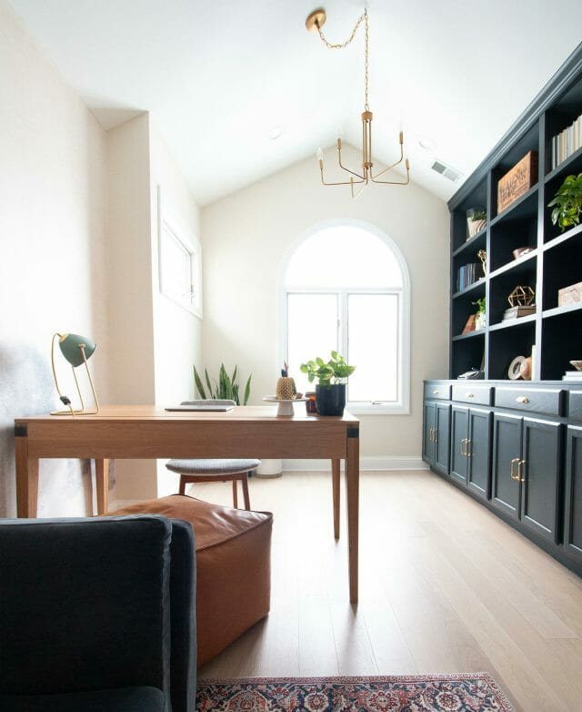 An arched, white room features black bookcases and the Madera Desk.