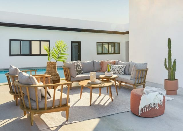 An outdoor sofa set is shown with a rug, cactus, and ottoman.