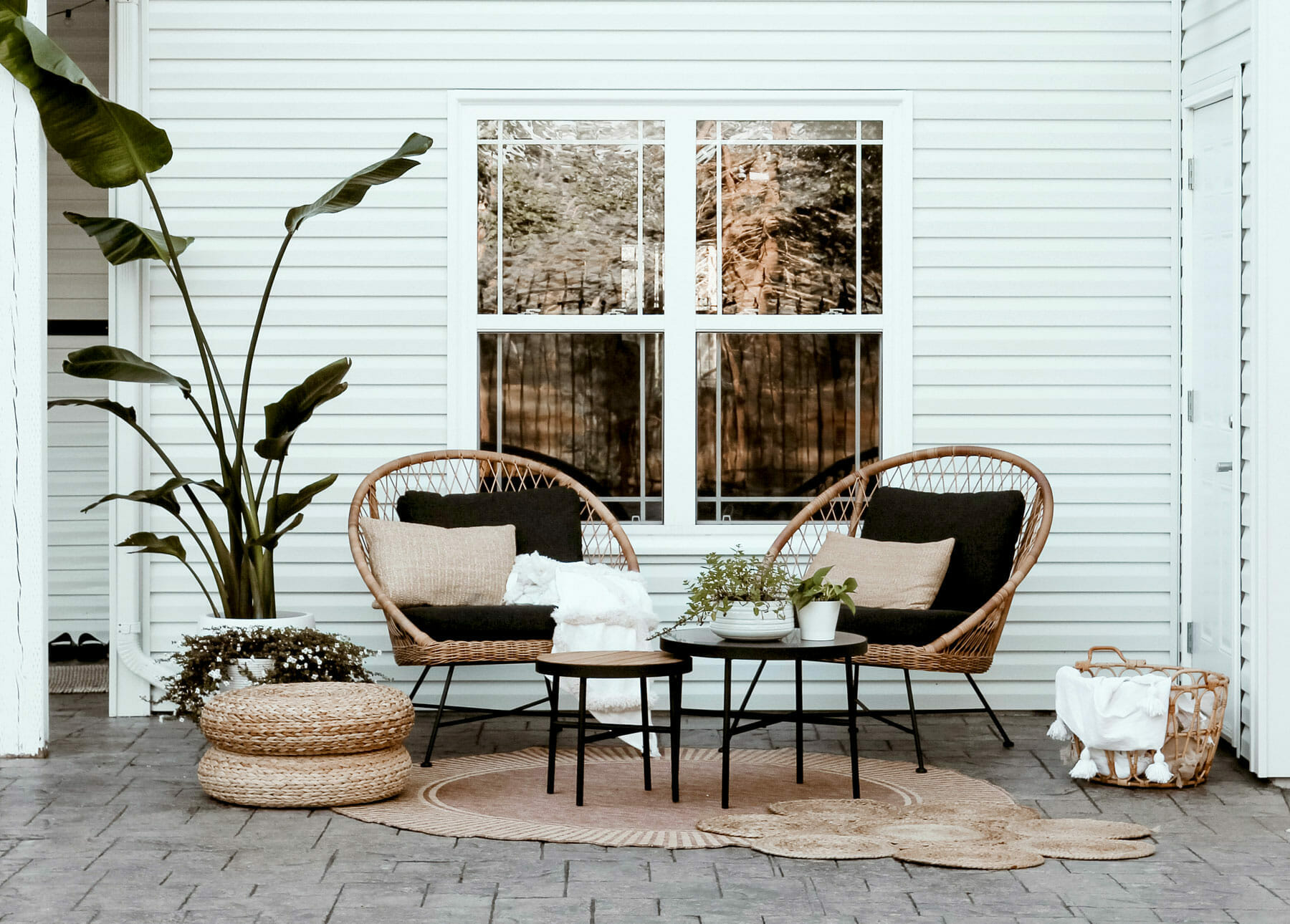 Two Aeri Lounge Chairs from Article are set up with a large plant and outdoor rug.