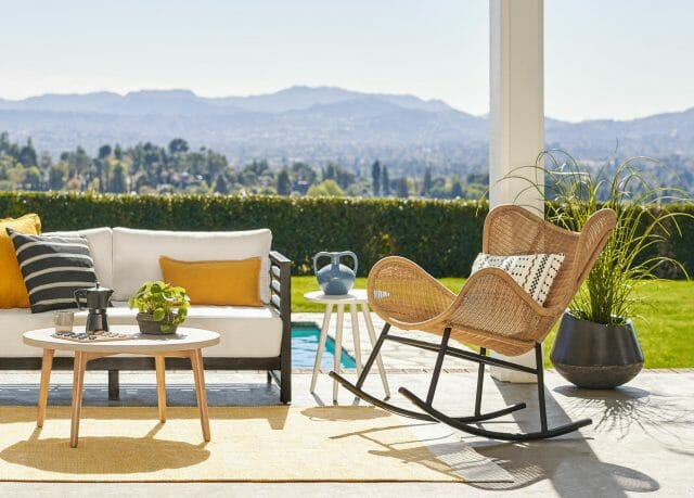 A Beltaine wicker rocking chair is shown on a sunny patio