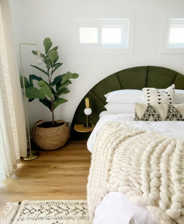 The bedroom of blogger Cottage and Sea is shown with a semi-circle green velvet headboard, fiddle-leaf fig plant, and white chunky throw.