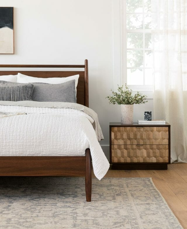 A walnut bed with white bedding is matched by a geometric nightstand.