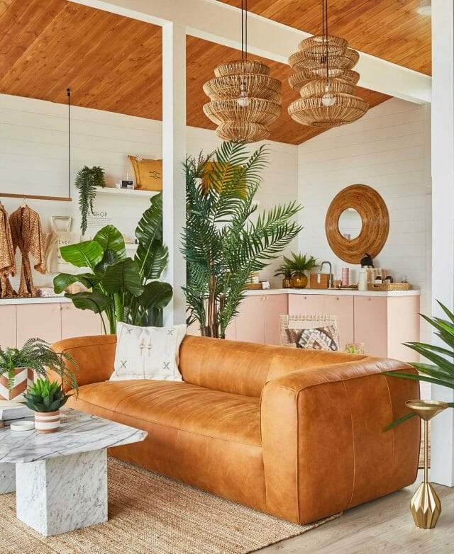 A tan leather sofa sits in the middle of a mid-century style room.