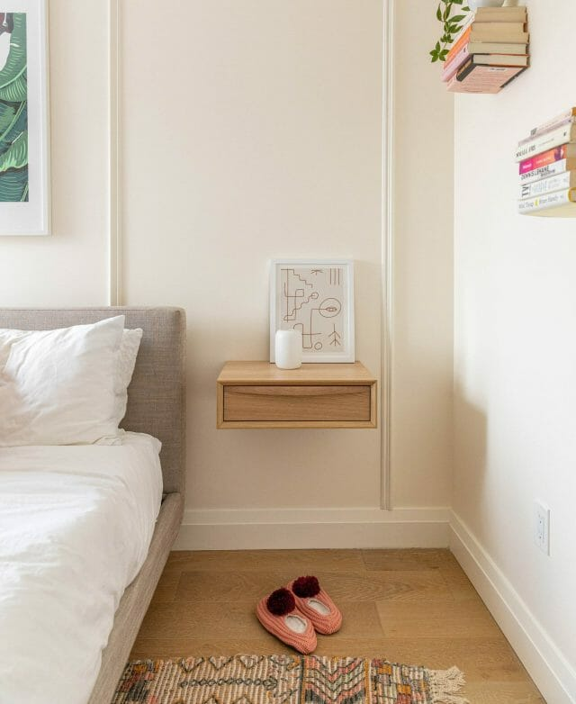 A floating nightstand features a framed minimalist art piece and pink slippers on the floor.