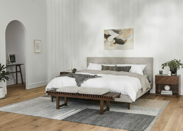 A gray bed frame is shown on top of a geometric rug.