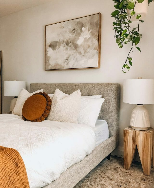 The bedroom of blogger Boneill At Home is shown with a gray bed and wood side table.